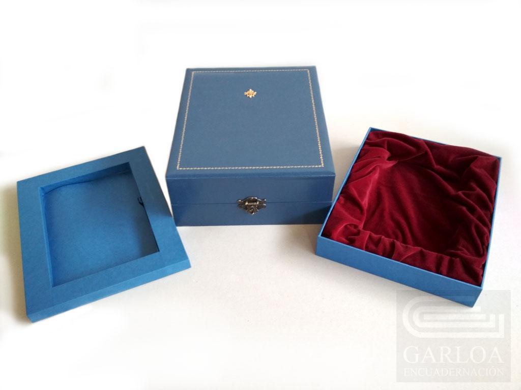 Caja de madera con cierre de metal y orlas y sello metálico en la tapa, con dos cajetines.
